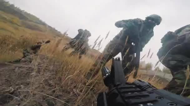 Point-of-view shot of squad of soldiers in camouflage uniform coming out of trenches in field continuing military operation armed with sniper rifles and guns