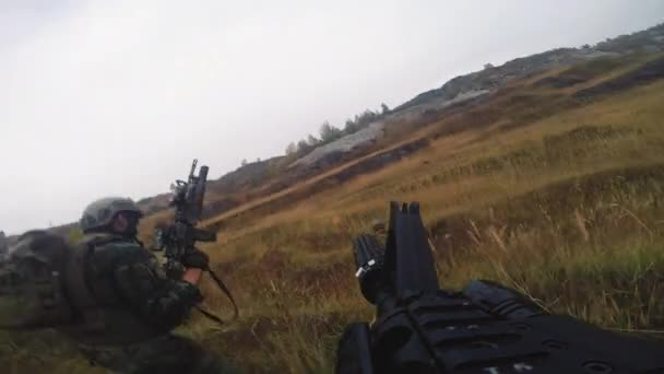 Point-of-view shot of squad of soldiers in camouflage uniform running through field armed with sniper rifles and guns