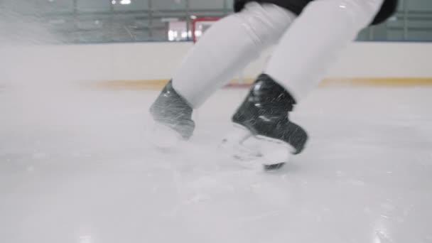 Nízké zpomalení nepoznatelného hokejisty v bruslích, který se náhle zastaví a kopne do ledu na kluzišti ostrými čepelemi