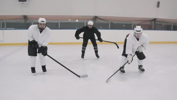 Slow-motion zoom-in shot of male hockey players in uniform and helmets standing in stance with sticks on empty ice arena looking at camera