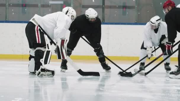 Panning plný záběr členů hokejového týmu v černobílých dresů a helmy stojící v kruhu s jejich hole připravené před zahájením hry