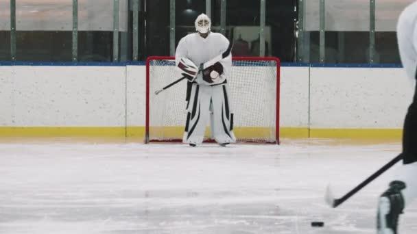 Kompletní záběr mladých mužských hokejistů trénink na ledové aréně uvnitř, střelba hokejový puk do brankářů sítě