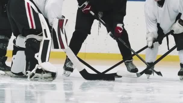 Nízké zpomalení nerozpoznatelných mužských hokejistů stojících v kruhu a poklepávajících hůlkami o led před zápasem
