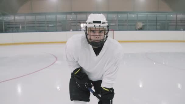 Zpomalený zoom-in střední portrét mladého bělocha mužského hokejisty v bílé uniformě a helmě s klecí stojící v postoji s holí na prázdné ledové aréně při pohledu do kamery