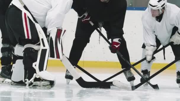 Naklonění-up záběr profesionálního hokejového trenéra v červené helmě a mladé mužské hráče stojící v kruhu na ledě při tréninku, diskutovat hokejové triky a techniky