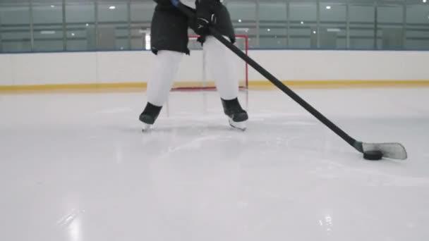 Nízký záběr nerozpoznatelného mužského hokejistu bruslení na prázdné ledové aréně kapající puk pohybující se směrem ke kameře