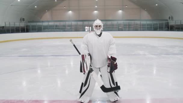 Pomalý zoom-out plný záběr portrét mužského hokejového týmu, jak stojí společně na ledové aréně a dívá se na kameru s brankářem na hlavě