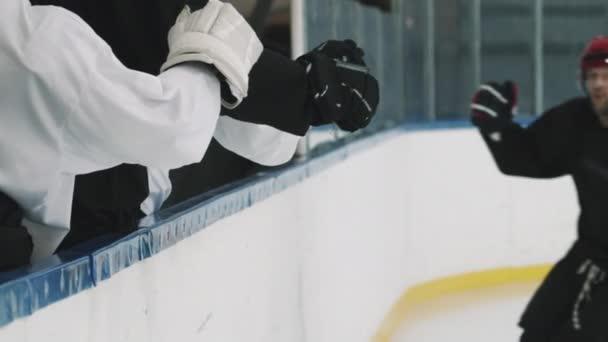 Střední záběr dospělého mužského hokejisty v červené helmě a černém dresu dává plácnutí členům týmu stojící na hráče tribune, zatímco bruslení kolem nich