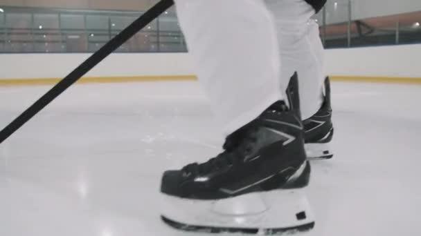 Nízký zadní pohled záběry nerozpoznatelného mužského hokejisty bruslení podél prázdného kluziště kapající hokejový puk