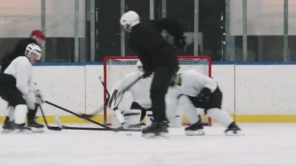 Kompletní záběr aktivních mužských hokejistů v dresech a helmách se snaží převzít kontrolu nad hokejovým pukem na kluzišti, zatímco brankář čeká na netu