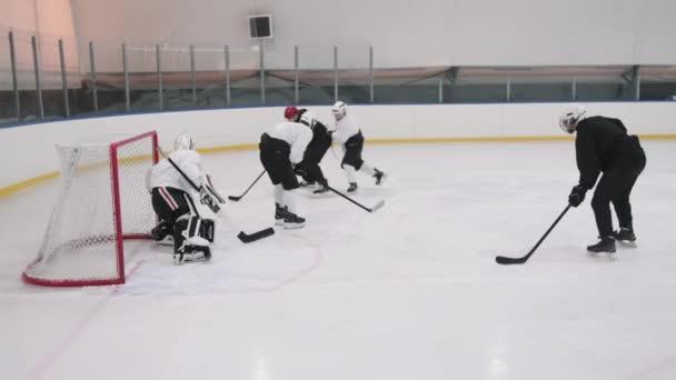 Slow-motion plný záběr hokejistů předává puk dopředu hráč v černé uniformě, vstřelil gól v brankářů brány a jásající vítězství s týmem