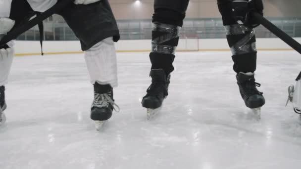 Panning low-section záběry mužských hokejistů nohy v bruslích a ochranné pomůcky stojící na kluzišti v souladu s brankář ve středu