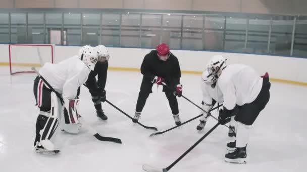 Full high-úhel záběr hokejového trenéra říká hráčům, aby zaujali své pozice a začali hrát v kryté ledové aréně