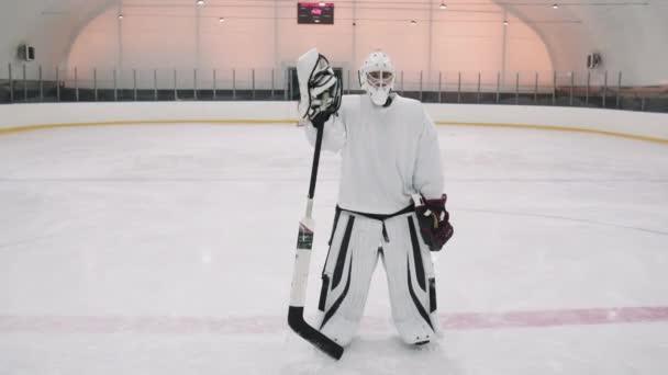 Full oblouk záběr portrét s zpomalením plně vybaveného hokejového brankáře stojící na prázdném kluzišti s holí při pohledu do kamery