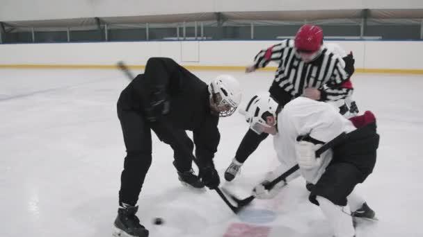 Slow-motion plný záběr hokejistů soupeřících týmů, kteří se snaží převzít kontrolu nad hokejovým pukem klesl oficiální v červené helmě a pruhované košili