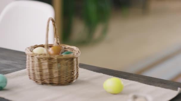 Közelkép aranyos kisfiú visel nyuszifül fejpánt néz körül, és lopás sárga húsvéti tojás az asztalról, majd bujkál
