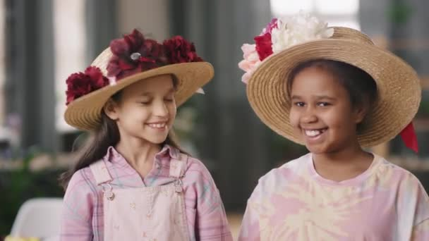 Portrait shot of happy girls in straw hats with flowers looking at each other and laughing, then smiling for camera
