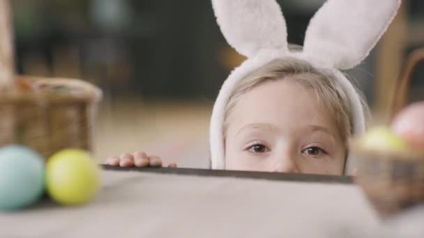 Zblízka rozkošný chlapeček nosí králičí uši čelenka šmírování na kameru zpoza stolu s košem a barvené velikonoční vejce