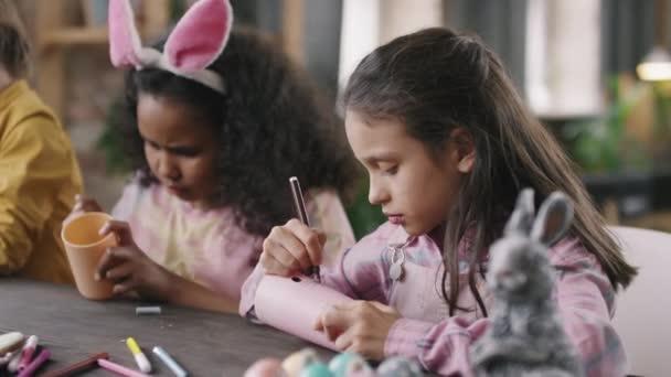 Ruční záběr roztomilé děti sedí u stolu a zdobení tužky poháry na Velikonoce během umění a řemesel třídy nebo dílny
