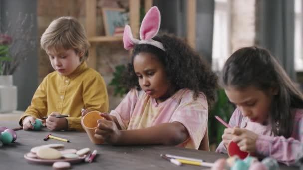 Közepes lövés aranyos gyerekek ül asztalnál a művészeti és kézműves osztály és díszítő húsvéti tojás és ceruza csésze