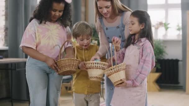 Naklonit záběr mladé ženy a roztomilé děti při pohledu na velikonoční vajíčka ležící v koších
