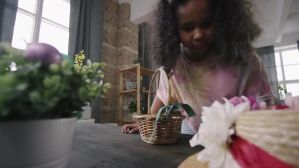 Cheerful black girl wearing bunny ears headband running around room during Easter eggs hunt