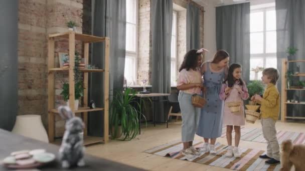 PAN záběr veselá žena mluví s dětmi s košíky a říká jim, aby začali hledat velikonoční vajíčka v místnosti