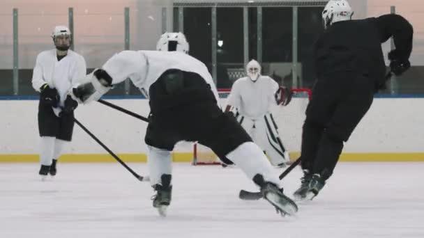 Zadní pohled plný záběr s pomalým soustředěným hokejovým brankářem chrání svou síť, zatímco dopředu hráči útočí ho snaží udeřit puk do něj