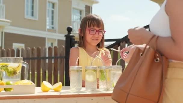 Derékig érő lövés egy vidám 10 éves lányról, aki friss házi limonádét árul egy nőnek, aki kint áll a diy stand előtt a forró nyári napon.