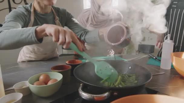 Zeitlupenaufnahme einer unkenntlich gemachten Frau beim Kochen während eines Kochkurses, die dem Braten grüner Bohnen etwas Sojasauce hinzufügt