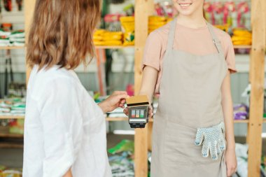 Brunette female customer holding credit card over payment terminal held by young smiling shop assistant of large gardening supermarket