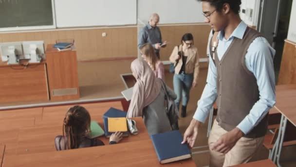 Vysokoúhlý pomalý záběr skupiny mladých multietnických studentů sedících u dlouhých dřevěných stolů v hledišti, kteří se navzájem zdraví před začátkem lekce