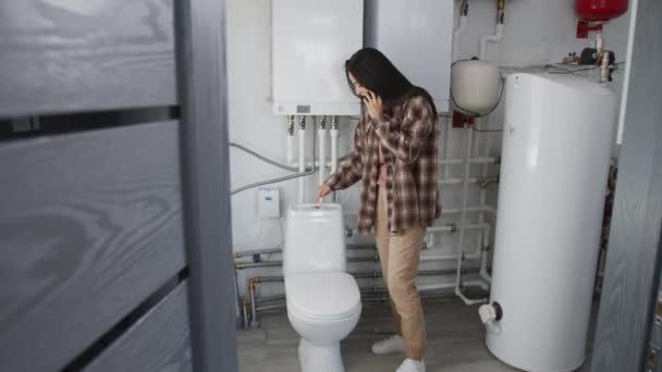 Ruční pomalý záběr mladé ženy stojící v koupelně a snaží se splachovat WC při rozhovoru s instalatérem na mobilním telefonu