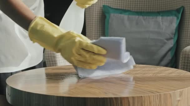 Slowmo close-up of housekeeper hands in rubber gloves cleaning and polishing surface of wooden coffee table in luxury hotel room