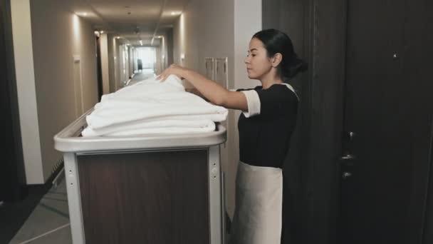 Střední záběr hospodyně s ručníky, ložním prádlem a čisticími potřebami na vozíku kráčející dlouhou chodbou, vstupující do hotelového pokoje pro čištění otvíracích dveří kartou