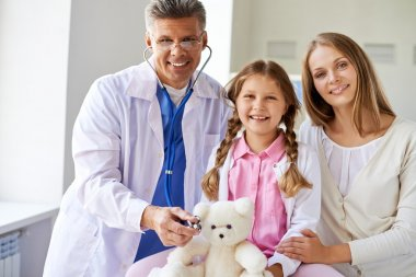 Smiling girl with teddy bear, her mother and doctor looking at camera in clinics stock vector