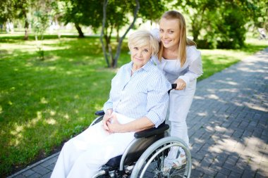 Female caregiver walking with senior patient