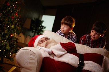 Boys looking at sleeping Santa Claus