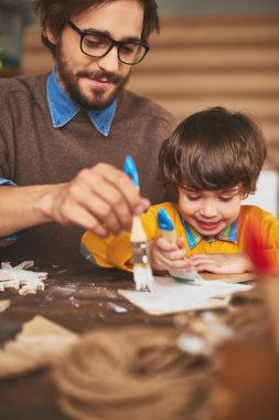Father and son painting wooden xmas tree