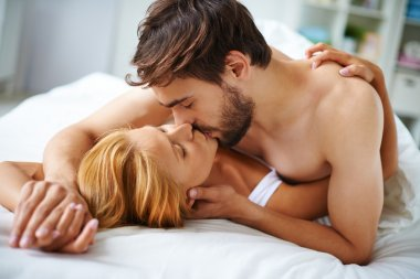 Couple lying on bed and kissing