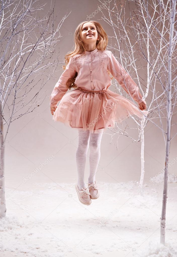 Girl jumping in winter forest