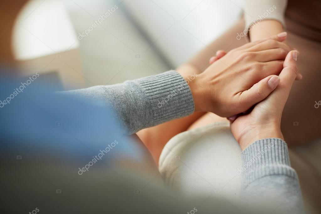 Psychiatrist hands holding palm of patient