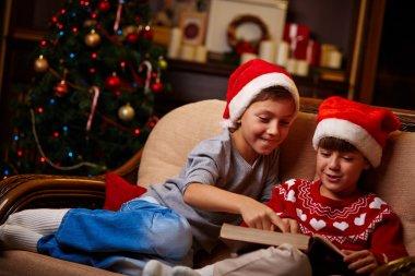 Children in Santa caps reading
