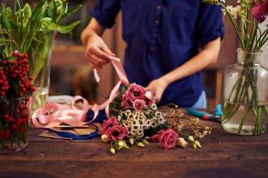 Florist tying rose bunch
