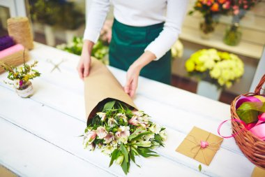 Florist selling bouquet of amaryllises