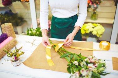 Florist tying up fresh flowers