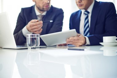 Businessmen with tablet discussing
