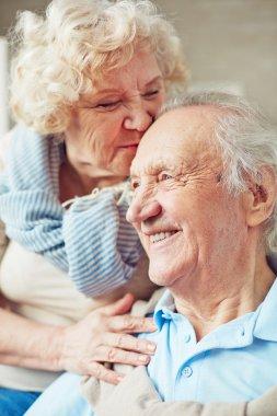 Elderly woman kissing husband