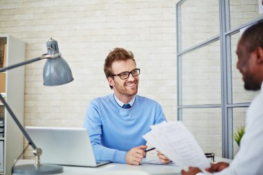 manager reading resume of man
