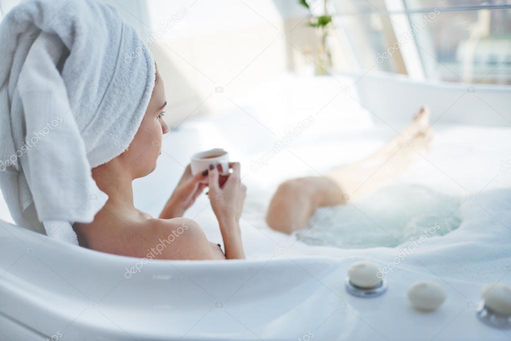 Femme Assise Dans La Baignoire Avec Une Tasse De The Photographie